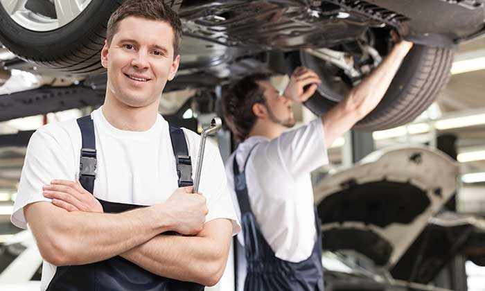two service technicians working on a car